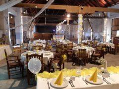 Scénické osvětlení svatební stodoly do žluto-bílé barvy.