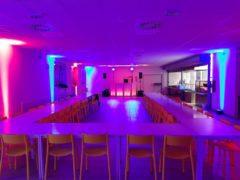 Podsvícená DJ stage a osvětlení stěn sálu.