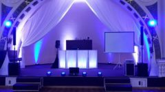 Pohled na instalaci stativového plátna a projektoru na pódiu.